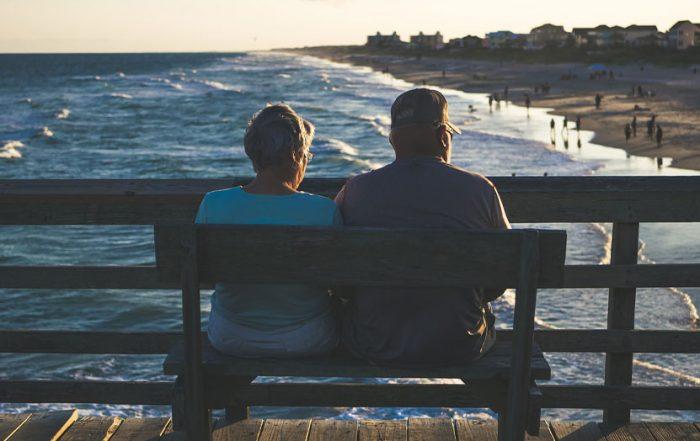 Älteres Eherpaar sitzt auf Pier und schaut aufs Meer