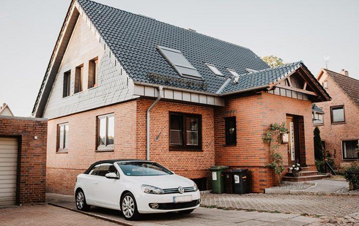 Foto eines Einfamilienhauses mit einem davor geparktem Auto