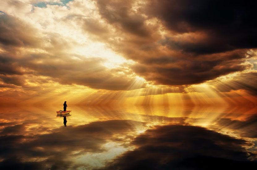 Mann auf einem Boot im Wasser bei einem Sonnernuntergang